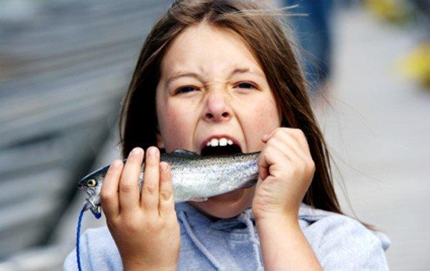 เด็กผู้หญิงกำลังกินปลา