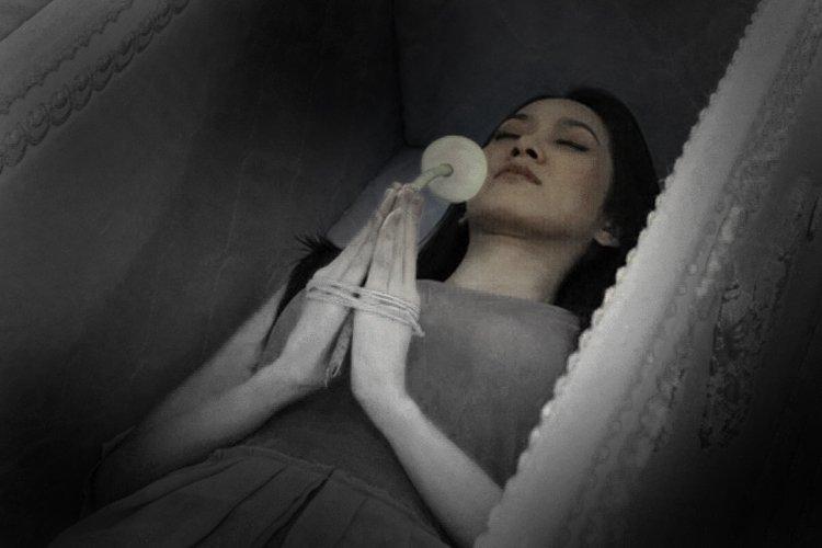 ผู้หญิงนอนอยู่ในโลงศพ